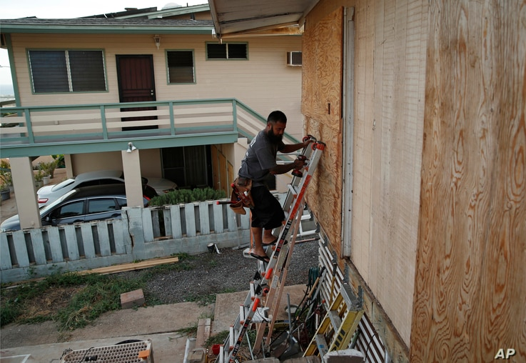 Kaipo Popa secures plywood to protect windows on a home in preparation for Hurricane Lane, Aug. 22, 2018, in Kapolei, Hawaii.