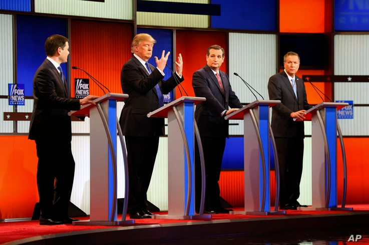 Republican presidential candidate, businessman Donald Trump, second from left, gestures as Sen. Marco Rubio, R-Fla., Sen. Ted Cruz, R-Texas, and Ohio Gov. John Kasich watch him a Republican presidential primary debate at Fox Theatre March 3, 2016, in...