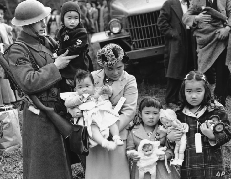 FILE - Cpl. George Bushy, left, a member of the military guard which supervised the departure of 237 Japanese people for California, holds the youngest child of Shigeho Kitamoto, center, as she and her children are evacuated from Bainbridge Island, W...
