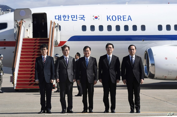 South Korea's national security director Chung Eui-yong, center, National Intelligence Service Chief Suh Hoon, second left,  and other delegators pose before boarding an aircraft as they leave for Pyongyang at a military airport in Seongnam, south of...