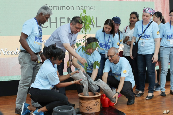 Malaysian Minister of Transport Anthony Loke, third from left, plants a tree with family members of passengers of the missing Malaysia Airlines Flight MH370 during a Day of Remembrance for MH370 event in Kuala Lumpur, March 3, 2019.