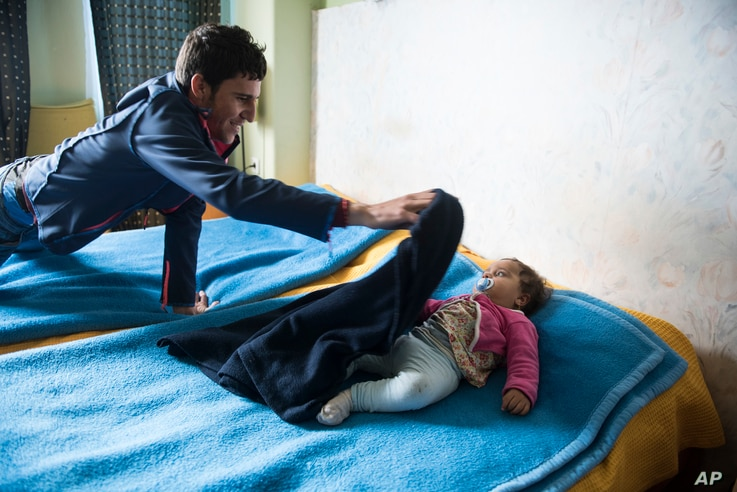 Shaker Mahie, 24, covers his 10-month-old daughter, Maria, inside the room of a hotel in the northern Greek village of Agios Athanasios, Dec. 21, 2017. As a member of a persecuted minority in Iraq, Shaker Mahie has seen his people massacred, raped an...