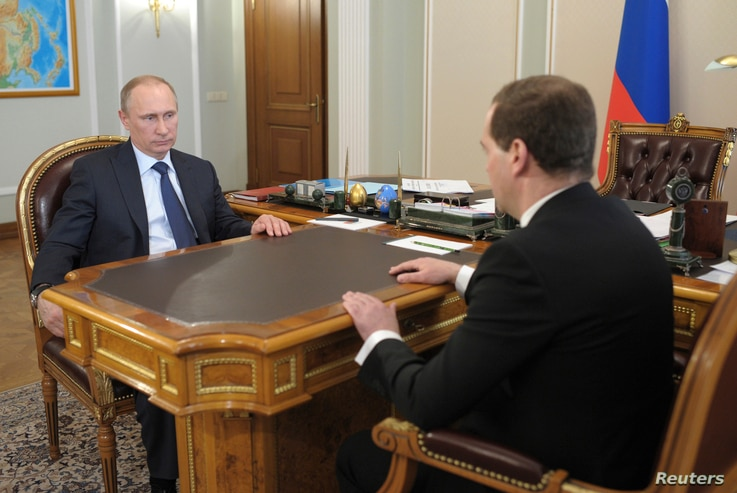 Russian President Vladimir Putin (L) talks with Prime Minister Dmitry Medvedev during their meeting at the Novo-Ogaryovo state residence outside Moscow, Apr. 19, 2014.