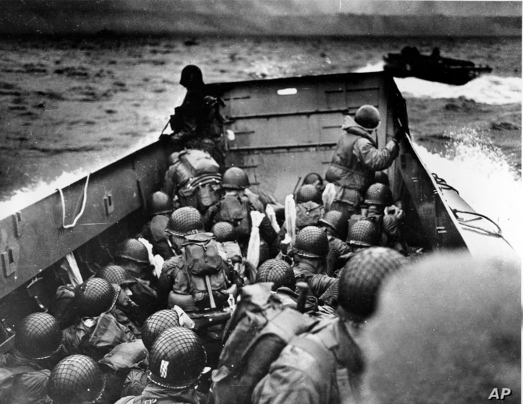 CORRECTS DATE OF PHOTO, REMOVES REFERENCE TO TODAY  - FILE - In this June 6, 1944, file photo, Allied troops crouch behind the bulwarks of a landing craft as it nears Omaha Beach during a landing in Normandy, France. The D-Day invasion broke through ...