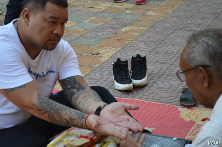 Sang Nin, 40, who was deported from the U.S. on Dec. 19, 2018, asks a fortune teller about his future while on a tour at Wat Ampe Phnom in Cambodia.