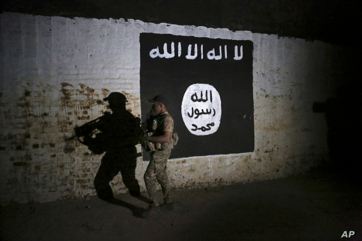 FILE - An Iraqi soldier inspects a train tunnel, adorned with an Islamic State group flag, that was used as training camp for IS fighters, in western Mosul, Iraq, March 1, 2017.