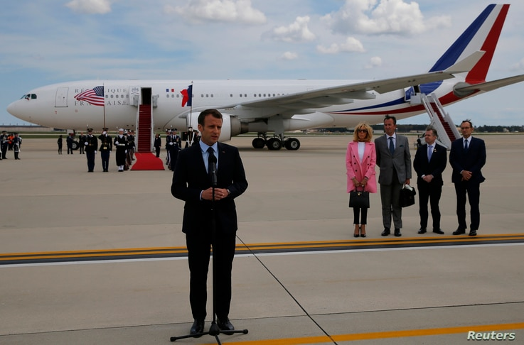 French President Emmanuel Macron speaks to the news media after arriving with his wife Brigitte Macron for their state visit to Washington at Joint Base Andrews in Maryland, April 23, 2018.