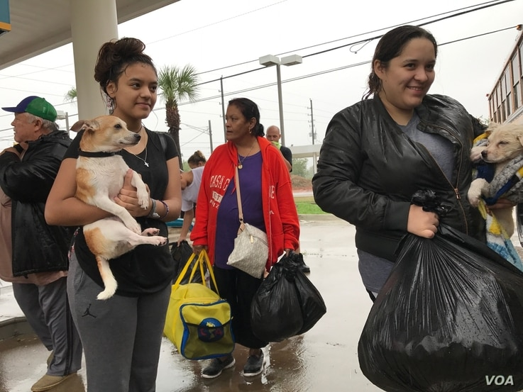 Rescued from flooding, people with their pets prepare to board a school bus bound for the M.O. Campbell Educational Center in north Houston, Texas, Aug. 27, 2017. The multipurpose facility is serving as a Red Cross shelter. (C. Mendoza/VOA)