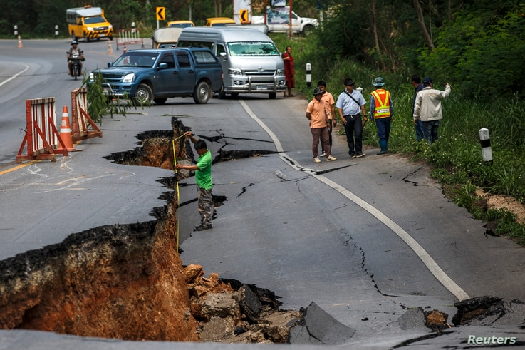 An officer measures a drop on a section of a highway road, which was damaged by Monday's earthquake in Chiang Rai, in northern Thailand, on May 6, 2014.