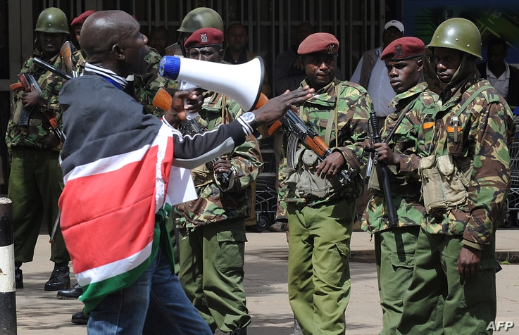 A supporter of presidential candidate Raila Odinga demonstrates on March 30, 2013 as Kenyan policemen keep vigil outside the Supreme Court in Nairobi.