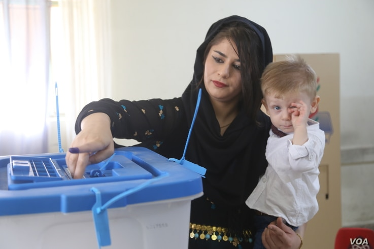 A Kurdish woman carries her baby while voting at a polling station during parliamentary elections in Sulaimaniah, Iraq, September 30, 2018.  (Photo: R Majeed/VOA/Kurdish)