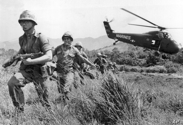 FILE - In this April 28, 1965 file photo, U.S. Marine infantry stream into a suspected Viet Cong village near Da Nang in Vietnam during the Vietnamese war. Filmmaker Ken Burns said he hopes his 10-part documentary about the War, which begins Sept. 17...