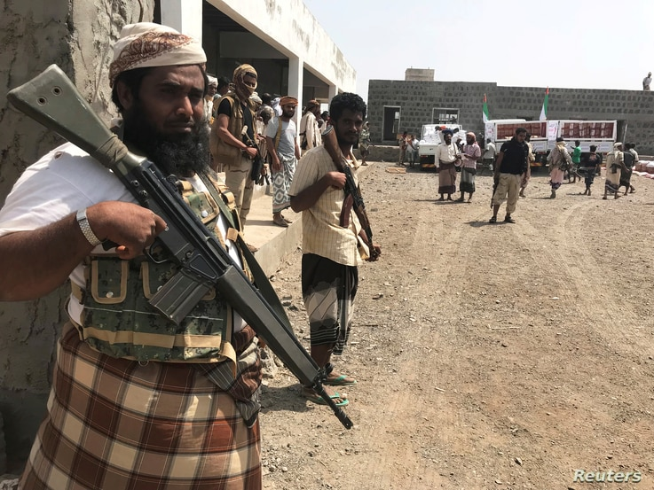 FILE - Yemeni fighters secure a building where UAE Red Crescent distribute aid to displaced people in Al-Mokha, Yemen, March 6, 2018.
