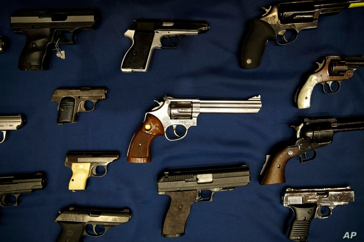 FILE - Guns seized by the police are displayed during a news conference in New York.