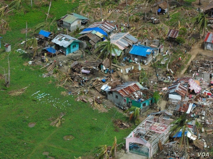 A devastated village in Eastern Samar province makes a plea for help, Philippines, Nov. 19, 2013. (Steve Herman/VOA)