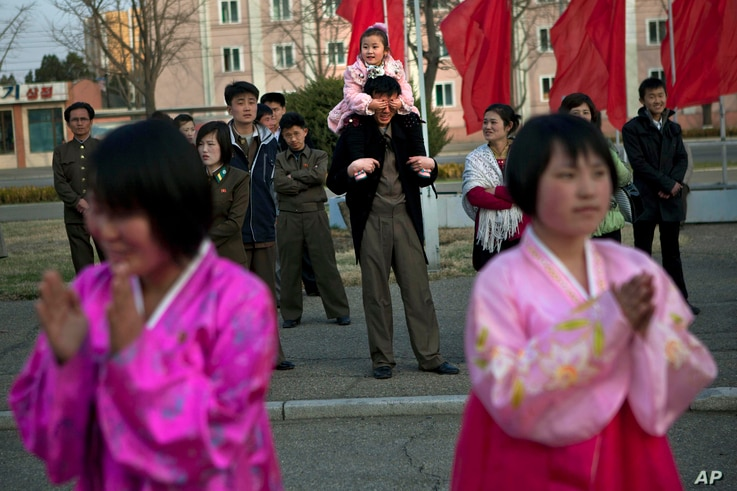 A North Korean child covers the eyes of her father as she sits on his shoulders watching mass folk dancing in front of Pyongyang Indoor Stadium in Pyongyang, April 15, 2013.