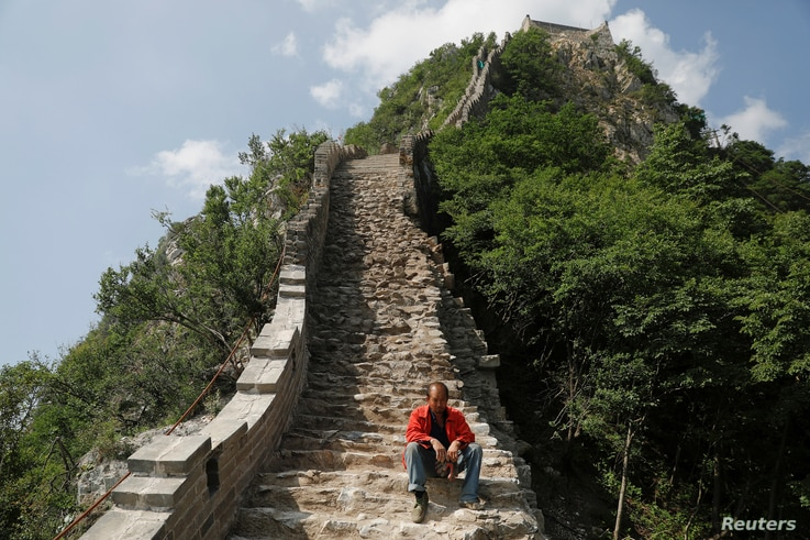 A man rests while working on the reconstruction of the Jiankou section of the Great Wall, located in Huairou District, north of Beijing, China, June 7, 2017.