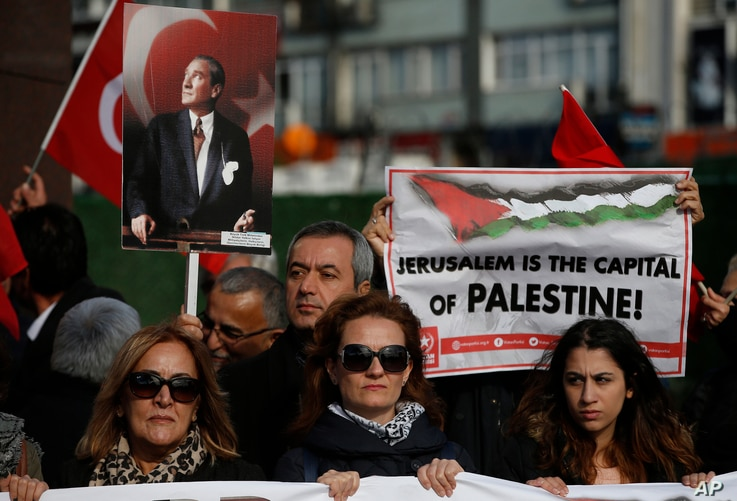 Protesters, holding Turkish and Palestinian flags and a placard of Mustafa Kemal Ataturk, the founder of modern Turkey, chant anti-U.S. slogans during a rally in Istanbul, Saturday, Dec. 9, 2017 against U.S. President Donald Trump's decision to recog...