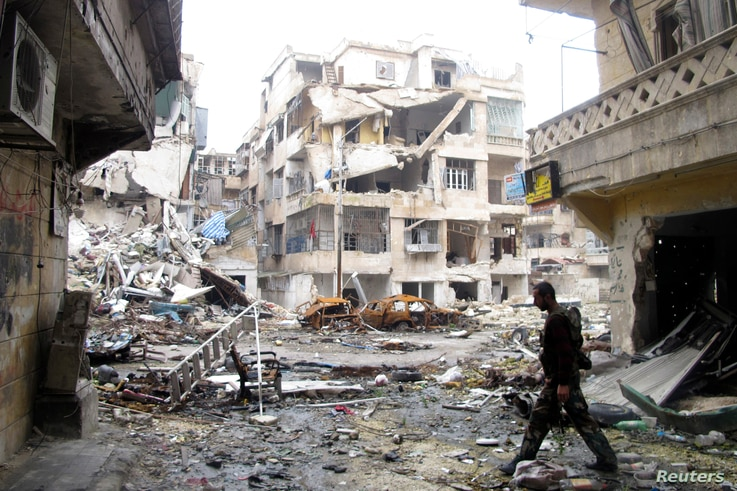 A Free Syrian Army member carries a weapon while walking down a debris-filled street in Aleppo's district of Salaheddine February 19, 2013.  REUTERS