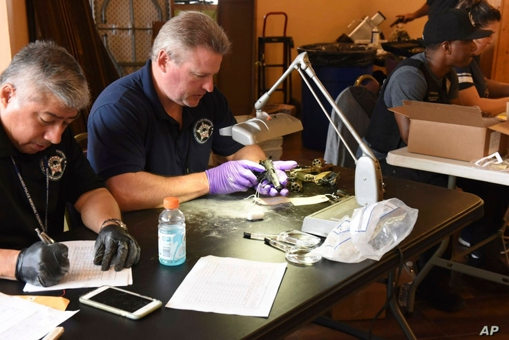FILE - Forensic firearms examiners inspect weapons turned in by residents in a gun buy-back program co-sponsored with the New Life Covenant Church Southeast in the 6th Police District, in this June 2, 2018, photo provided by the Chicago Police Depart...