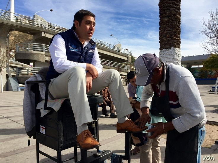 Nogales, Sonora Mayor Temo Galindo makes an unannounced exit from Municipal Hall to greet city residents and arrange a quick shoe shine.  (Photo: R. Taylor/VOA)