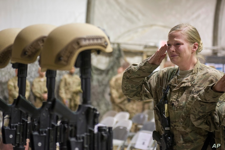 A U.S. service member salutes her fallen comrades during a memorial ceremony for six Airmen killed in a suicide attack, at Bagram Air Field, Afghanistan on Wednesday, Dec. 23, 2015.