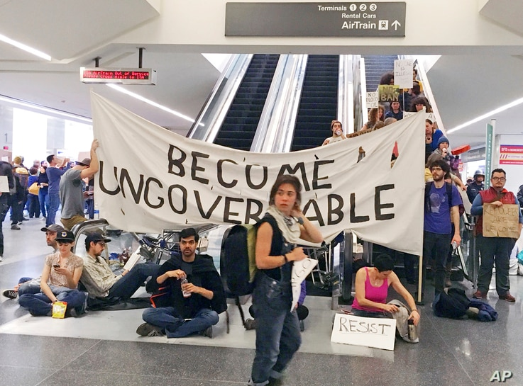 Demonstrators block an escalator at the international terminal in protest of President Donald Trump's executive order banning travel from seven Muslim-majority countries at San Francisco International Airport, Jan. 29, 2017.