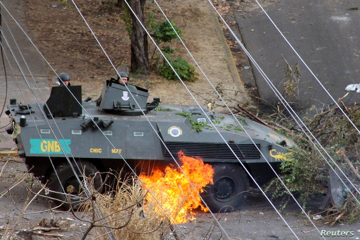 National Guards look on at a fire under the tank they are in, started after the tank was hit by a Molotov cocktail, during a protest against Venezuelan President Nicolas Maduro's government in San Cristobal, about 410 miles (660 km) southwest of Cara...