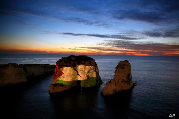 The landmark Raouche sea rock is illuminated by a giant Palestinian flag in Beirut, Lebanon, Saturday, Dec. 9, 2017. Arab countries are condemning the Trump administration's decision to recognize Jerusalem as the capital of Israel with mass protests ...