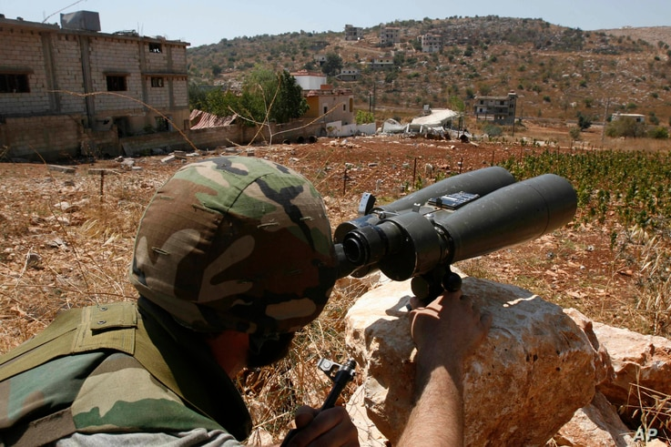 FILE - A Hezbollah fighter uses binoculars to scan for Israeli forces' positions, on the outskirts of the village of Aitaroun, near the town of Bint Jbeil, Aug. 16, 2006.