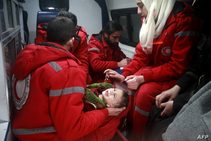 Syrian staff from the International Committee of the Red Cross evacuate a baby in Douma in the eastern Ghouta region on the outskirts of the capital Damascus.