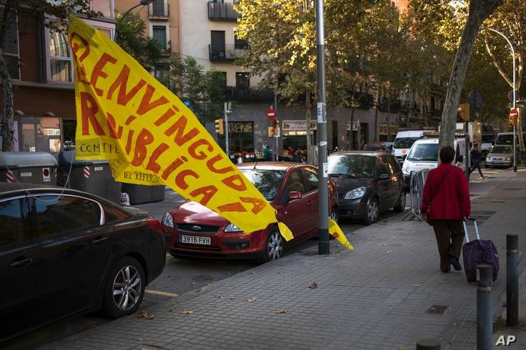 """A woman walks past a torn down placard reading in Catalan """"Welcome Republic"""" in Barcelona, Spain, Oct. 11, 2017."""