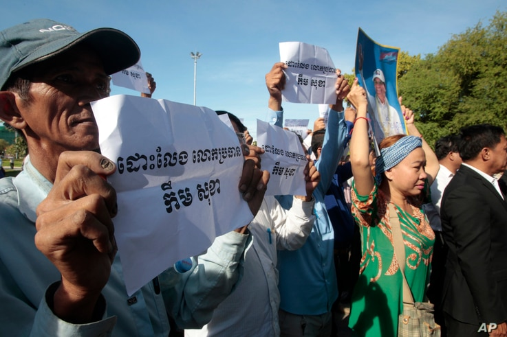 """Supporters of the opposition Cambodia National Rescue Party hold a portrait of party leader Kem Sokha and slogans that read: """"Free Kem Sokha"""" during a rally near an appeals court in Phnom Penh, Cambodia, Sept. 26, 2017."""