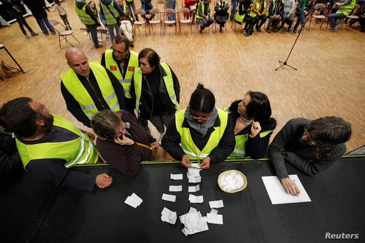 Protesters wearing yellow vests, the symbol of a French protest against higher diesel fuel prices, count ballots as they elect a representative to liaise with other blockade points, in Aubevoye, France, Dec. 6, 2018.