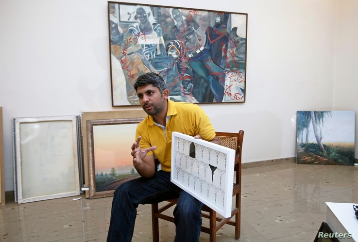 Imran Mudassar, 31, a fine art teacher, shows his latest piece Government College University in Lahore, Pakistan, March 22, 2013.