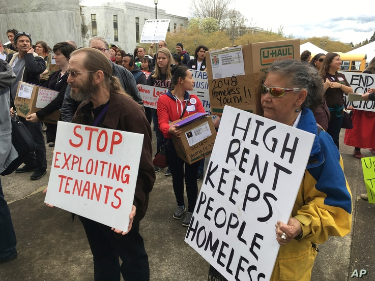 FILE - Supporters of a bill to ban most no-cause evictions of home renters in Oregon demonstrate on the Capitol steps in Salem, April 12, 2017. Oregon on Feb. 28, 2019, became the first state in the nation to impose mandatory rent control.