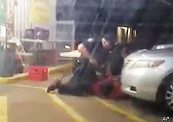 In this July 5, 2016, photo made from video, Alton Sterling is held by two Baton Rouge police officers, with one holding a hand gun, outside a convenience store in Baton Rouge, Louisiana.