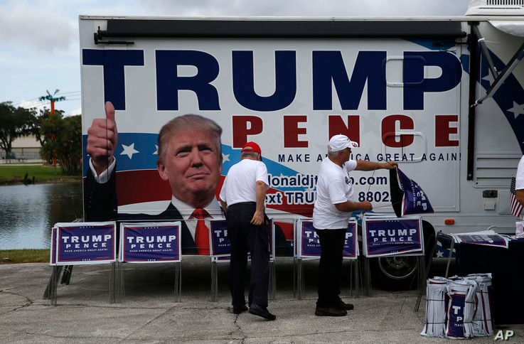Campaign volunteers prepare signs before a speach by Republican presidential candidate Donald Trump at a campaign rally in Tampa, Florida, Aug. 24, 2016.