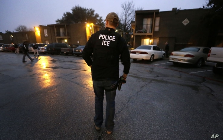 U.S. Immigration and Customs Enforcement agents enter an apartment complex looking for a specific undocumented immigrant convicted of a felony during an early morning operation in Dallas, March 6, 2015,.