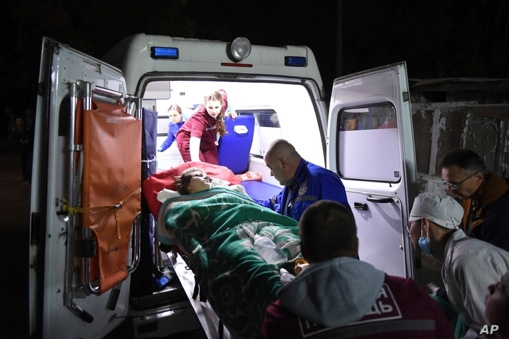 Medics load an injured person into an ambulance, in Kerch, Crimea, Oct. 17, 2018, following a shooting rampage at a vocational school.