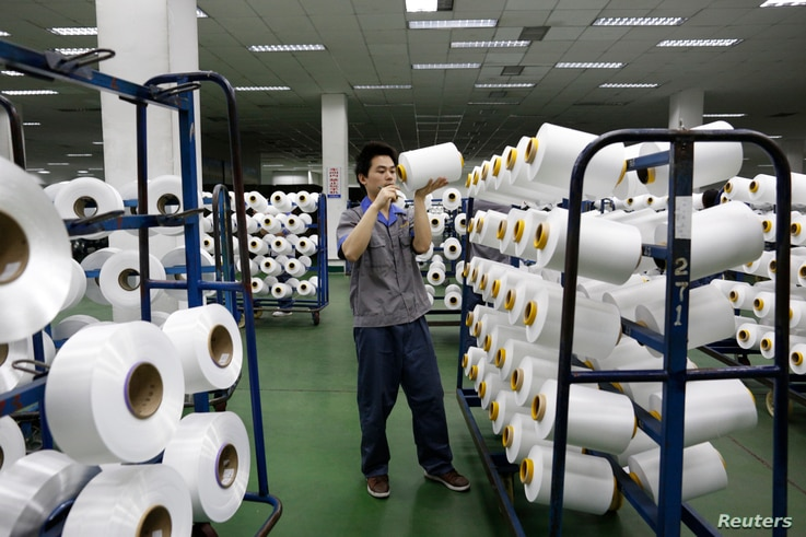 FILE - An employee works inside a textile mill in Yiwu, Zhejiang province.