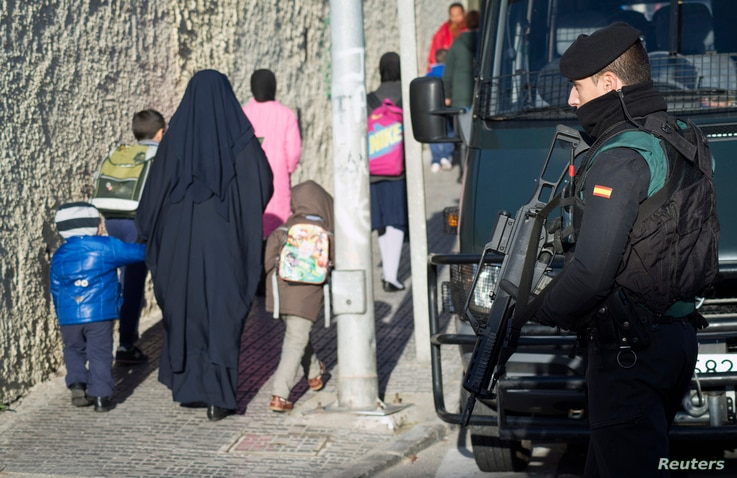 FILE - A Spanish civil guard holds his gun as women and children walk up a street during an operation to detain two men suspected of using social media to recruit people to violent groups like the Islamic State, in Spain's North African enclave Melil...