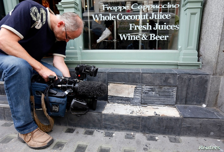 A camera man films broken slates outside a cafe in London, Sept. 3, 2013. Local media reported the tiles had shattered from sunlight reflected by the Walkie Talkie tower in London.