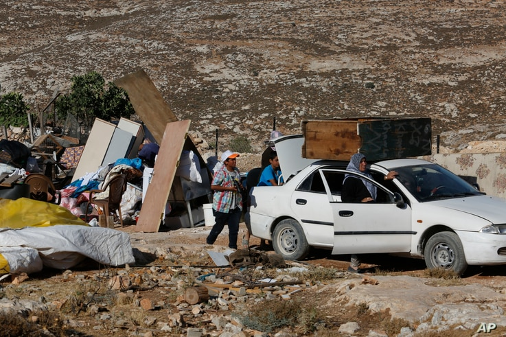 In this Tuesday, August 16, 2016 photo, Palestinians pack their belongings after their family house was demolished by Israeli troops in the West Bank village of Sair, near the town of Hebron.