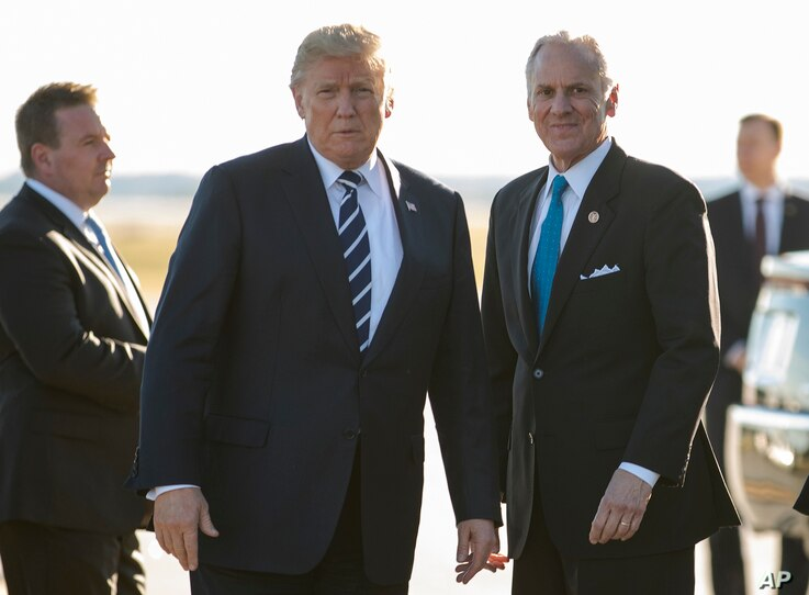 President Donald Trump stands on the tarmac with South Carolina Gov. Henry McMaster as he arrives on Air Force One at Greenville Spartanburg International Airport, in Greer, S.C., Monday, Oct. 16, 2017, en route Greenville, S.C., for a fundraiser for...