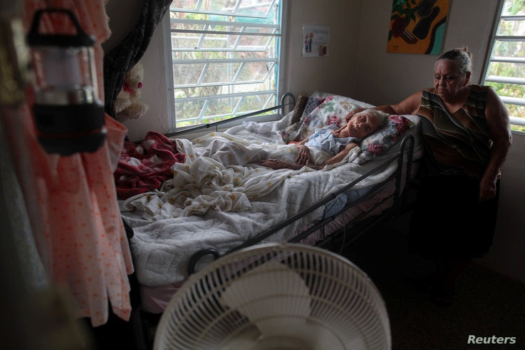 """Carmen Rodrigues stands by her bedridden mother, Rosa Maria Torres, 95, after Hurricane Maria destroyed the town's bridge in San Lorenzo, Morovis, Puerto Rico, Oct. 5, 2017. The family are trying to get Torres airlifted out of the town. """"If they don'..."""
