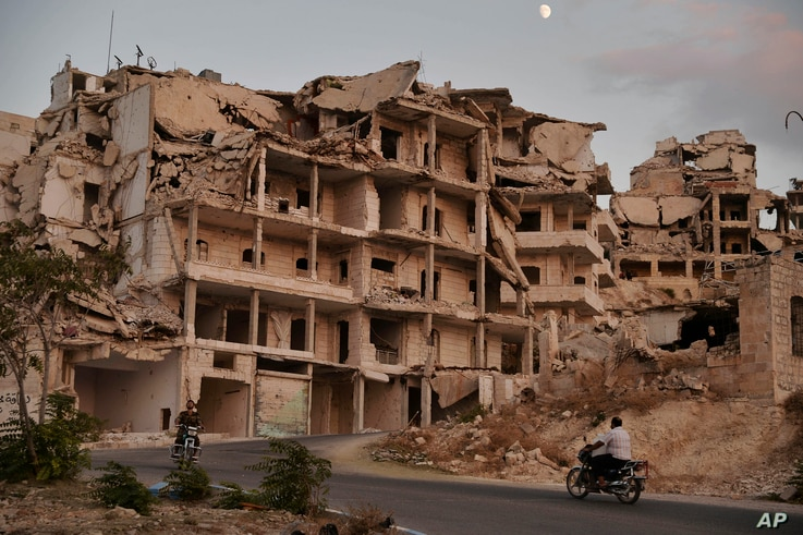 In this Sept. 20, 2018 photo, motor cycles ride past buildings destroyed during the fighting in the northern town of Ariha, in Idlib province, Syria. Ariha is one of five main towns in Idlib province and the last place to fall to rebel control in 201