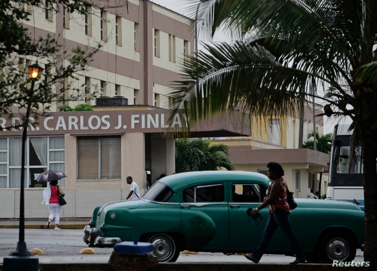 People walk beside the Carlos J. Finlay Military Hospital where U.S. government contract worker Alan Gross is held prisoner in Havana, March 19, 2013.