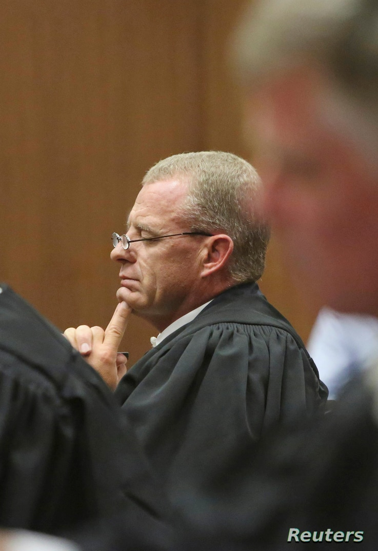 Prosecutor Gerrie Nel listens as Judge Thokozile Masipa delivers judgment during the appeal by prosecutors against the verdict and sentence of Oscar Pistorius in the North Gauteng High Court in Pretoria, December 10,  2014. South African prosecutors ...