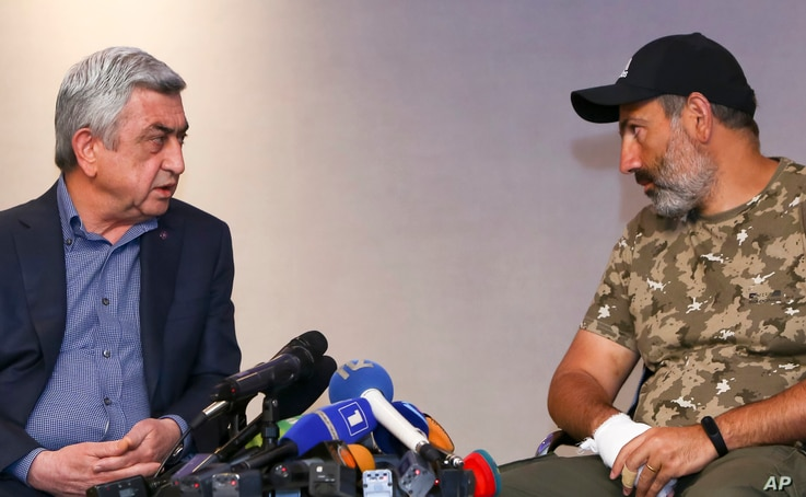 Serzh Sargsyan, left, speaks with protest leader Nikol Pashinian during their meeting in Yerevan, Armenia, April 22, 2018. (Hrant Khachatryan/PAN Photo via AP)